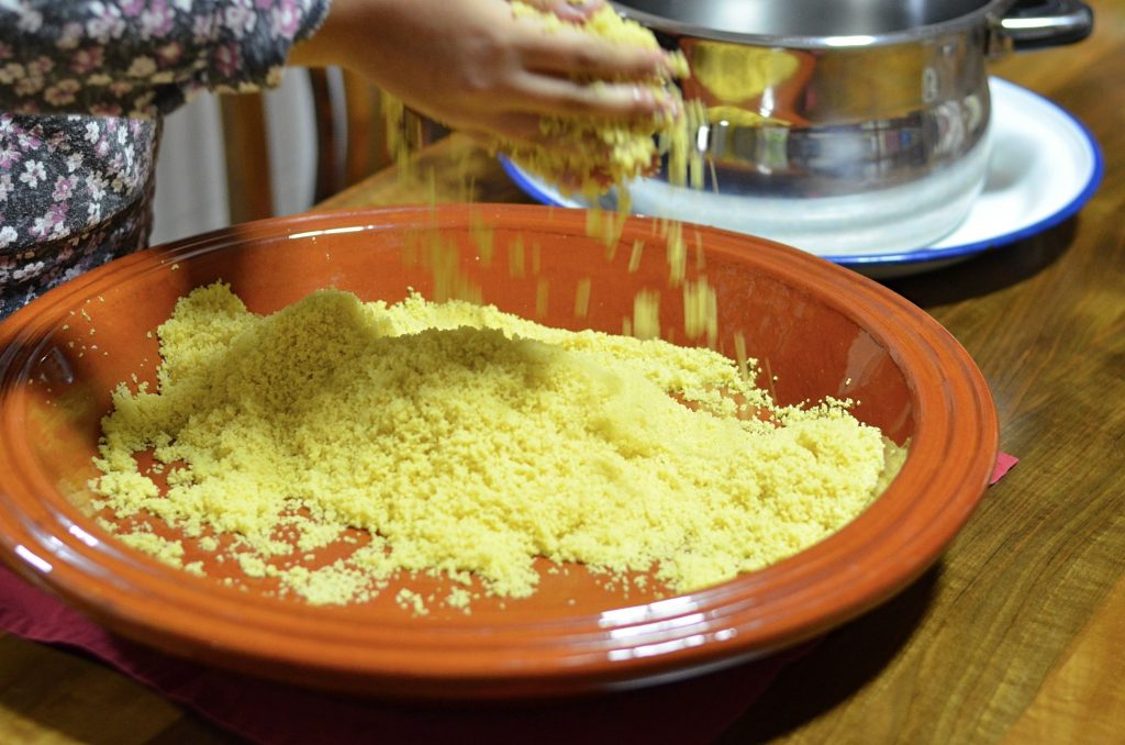 Couscous is falling from a pair of hands into a large shallow dish. The couscous is being tossed with water.
