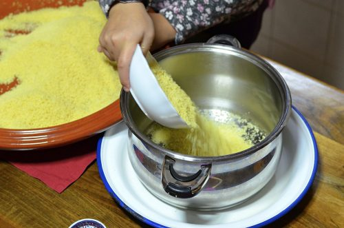 Overhead photo showing couscous being poured into a steamer basket from a bowl. A hand is holding the bowl and a large shallow dish of couscous can be seen in the background.