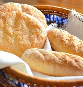 Photo of gluten-free Moroccan bread. Two gluten-free round loaves and two gluten-free mini-baquettes sit on a white linen napkin in a bread basket on a wooden table.