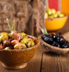 Marinated olives in bowls on wooden surface. The foremost bowl is in focus while two other bowls are shown in the background.