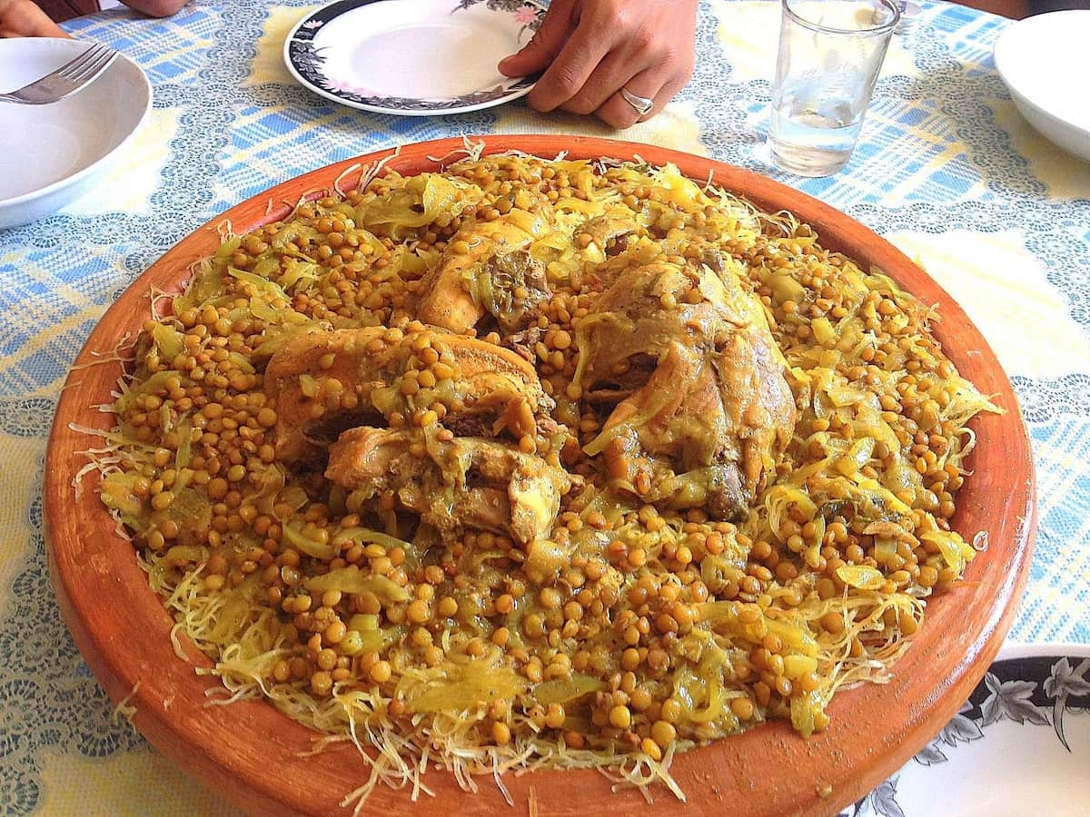 Photograph of a large, deep ceramic dish holding a Moroccan dish of chicken, lentils and onions served on a bed of shredded, stringy pan-fried crepes called rezzat el qadi.