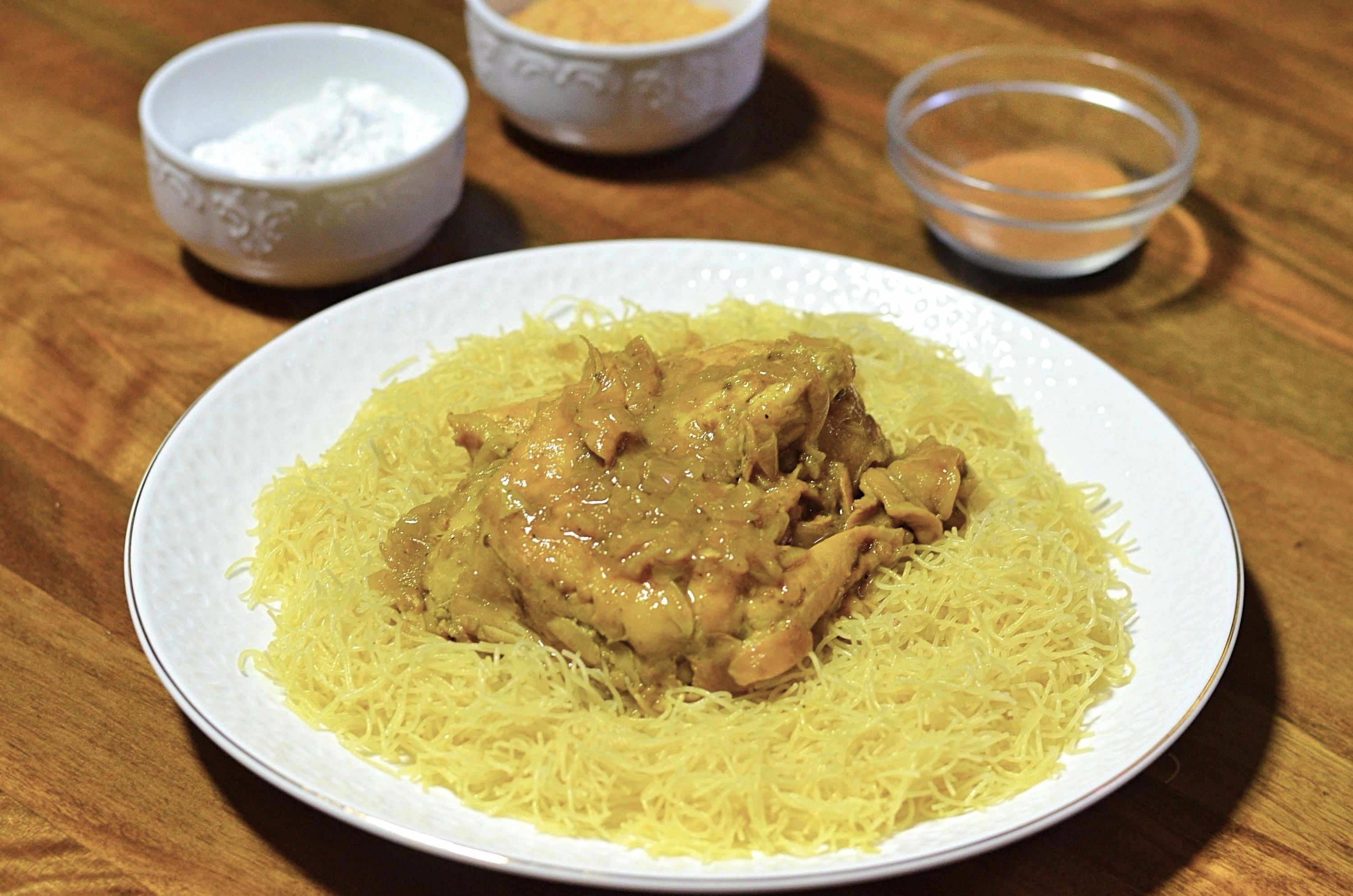 Chicken with a saffron onion sauce sits atop a bed of steamed broken angel hair pasta.
