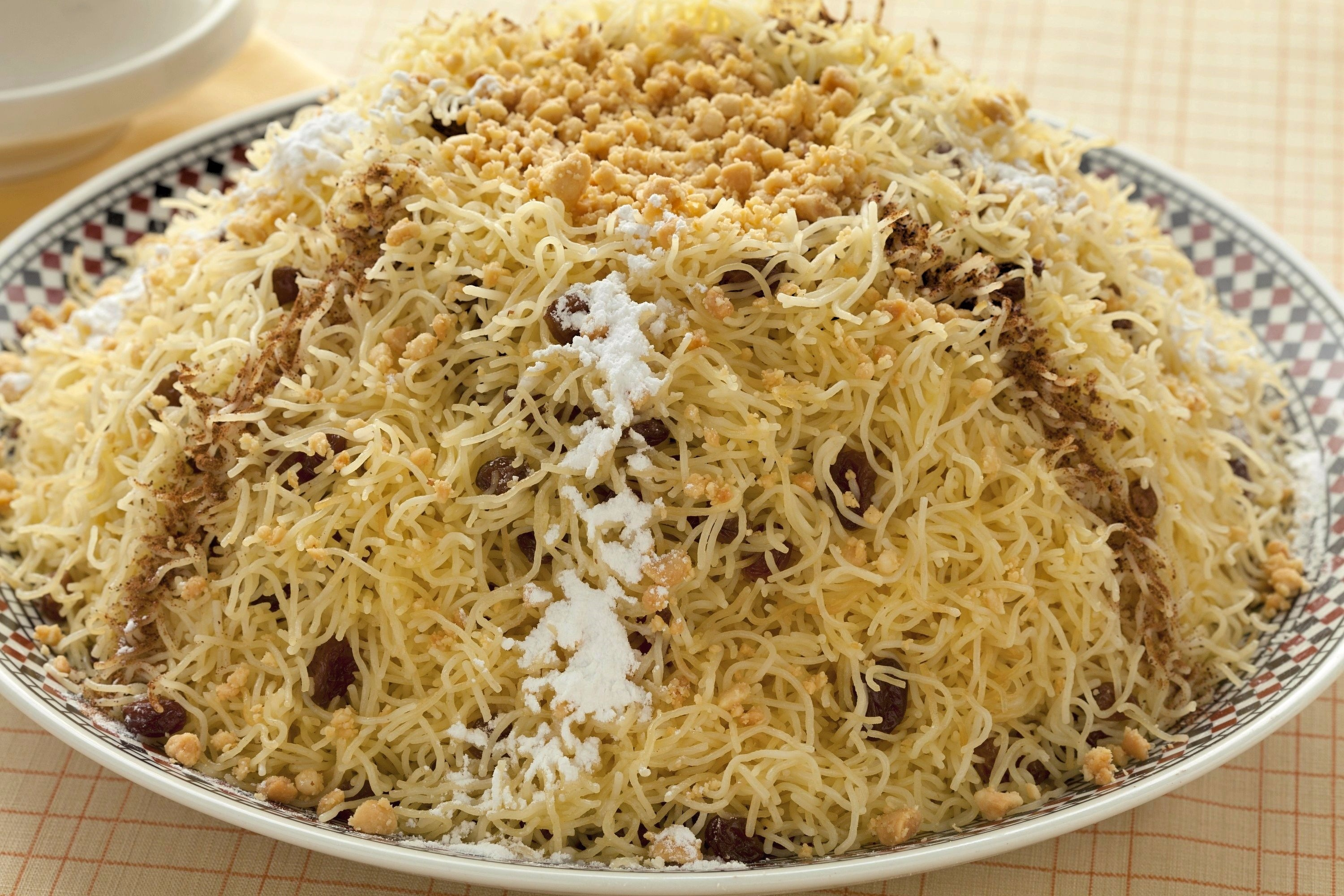 Steamed, broken strands of vermicelli are mounded high on a platter and decorated ground fried almonds, cinnamon and powdered sugar. Raisins can be seen throughout the vermicelli.