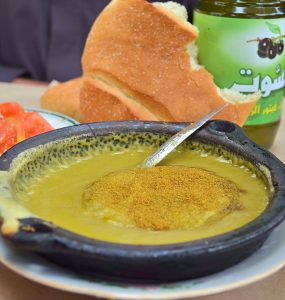 Moroccan split pea soup in a black shallow metal dish. The soup is garnished with ground cumin and olive oil. A spoon is in the soup and a partial loaf of Moroccan bread and bottle of olive oil are behind the bowl.