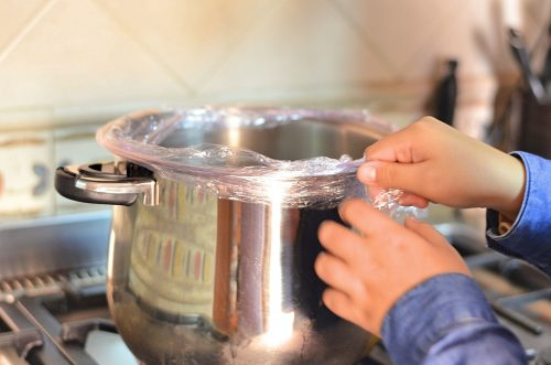 Hands are shown draping a folded length of clear kitchen plastic wrap over the rim of a large pot.
