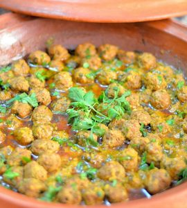 Marble-sized meatballs and buttey sauce in an unglazed tagine. The dish is garnished with a sprig of fresh cilantro.