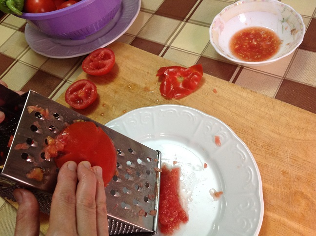 Image showing a hand grating a tomato half against a box grater.