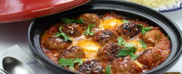 Small Moroccan meatballs and poached eggs in tomato sauce sauce are ready to be served from a tagine. The dish is garnished with fresh parsley and part of the red conical lid can be seen resting against the tagine base.