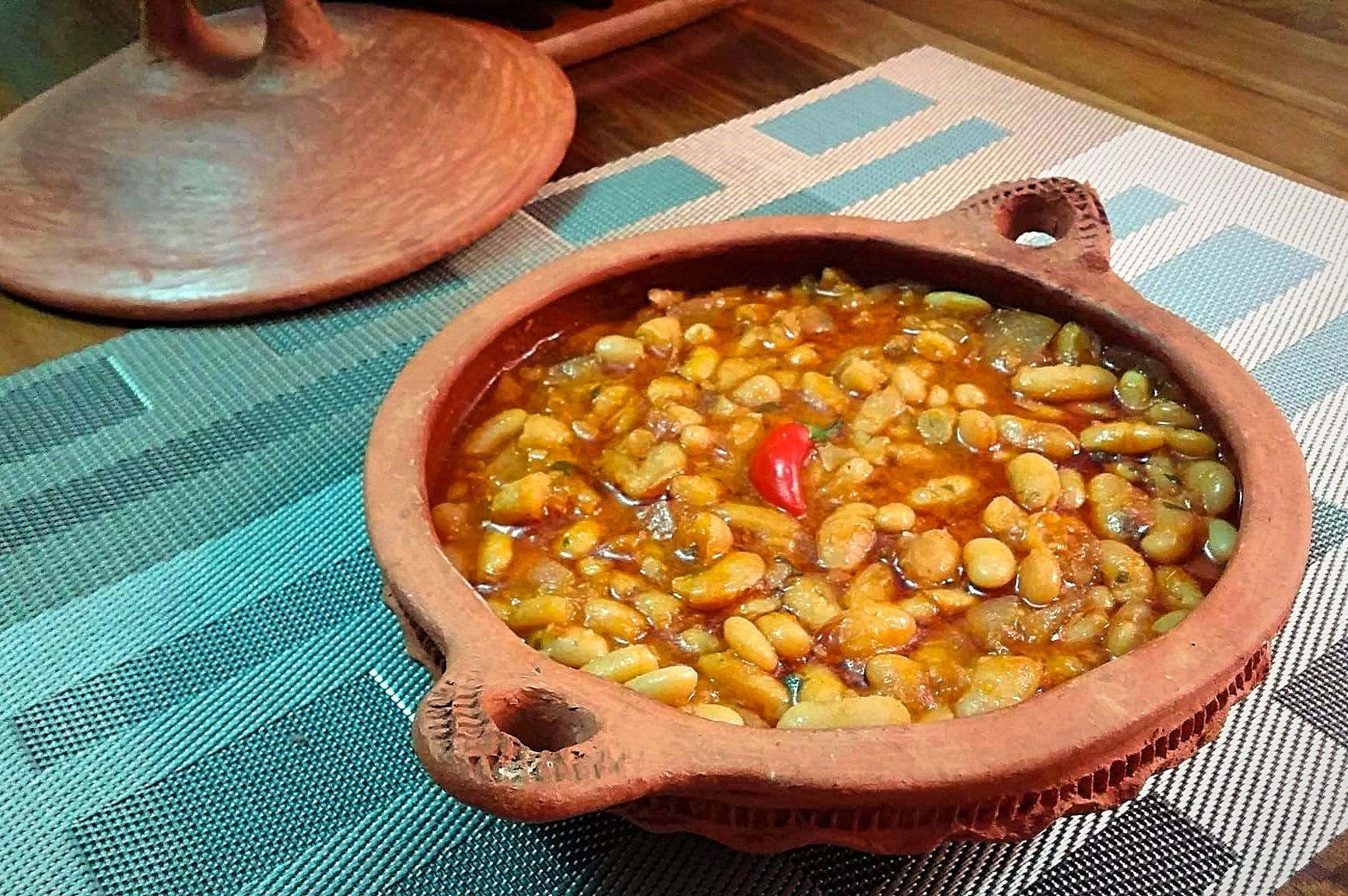 A shallow clay dish with handles holds Moroccan loubia, a dish of white beans stewed in zesty tomato sauce. A small red chili pepper is centered in the dish.