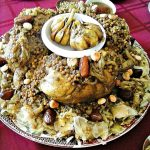 A platter of a Moroccan chicken and lentil stew served over a bed of shredded pastry. A whole chicken is centered on the pastry bed. Whole garlic cloves sit in a bowl on top of the chicken. The entire dish is garnished with dates and fried almonds.
