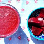 Overhead view of a large glass of Moroccan beetroot juice sitting next to a bowl of cooked beets.