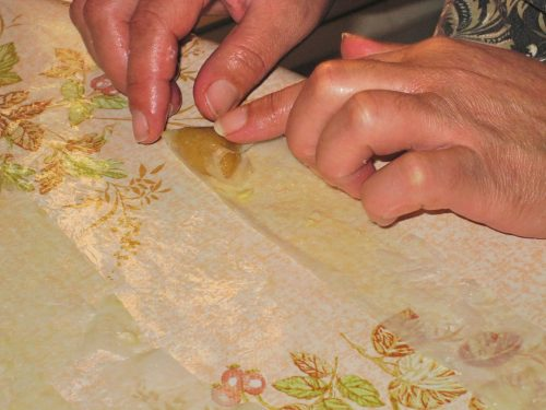 Close-up photo of hands folding almond paste into a triangular pastry with a narrow strip of warqa pastry.