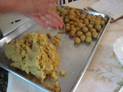 Almond paste on a baking sheet. Some of the paste has been shaped into balls.