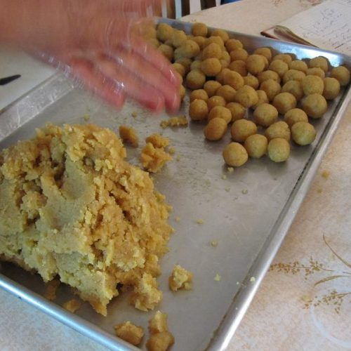 An aluminum baking tray holds a mound of almond paste on one side and balls of almonds paste on the other. Hands can be seen shaping the almond paste.