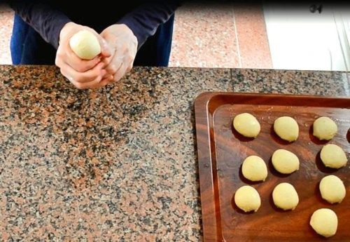 Overhead view of hands shaping a ball of dough while making meloui. Other balls of dough are arranged on an oiled plastic tray.