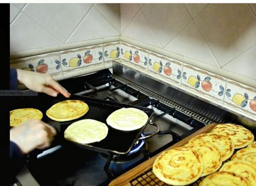 Round laminated pancakes called meloui are shown cooking on a double griddle. Two hands are blurred as they get ready to turn the dough. Fully cooked meloui sit on a rack in the foreground.