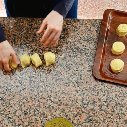A ceramic knife sits next to four sliced rounds of rolled dough on a granite counter top. Hands are slightly blurred as they transfer the rounds to an oiled plastic tray.