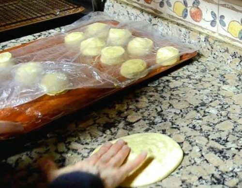 A hand is shown flattening a roll of dough on a granite counter into a round Moroccan pancake called meloui. In the background is a plastic tray holding roll of dough loosely covered with plastic.