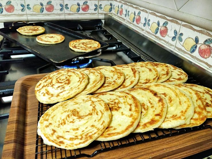 Freshly-made round Moroccan pancakes called meloui are on a cooling rack set on a tray. Three of the pancakes can be seen cooking on a griddle in the background.
