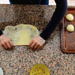 Hands are shown rolling a paper-thin square of dough on a granite counter. A bowl of oil and plastic tray holding balls of dough are also in the image.