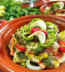 A tagine base is filled with carefully arranged fish and vegetables. In the background are another prepped fish tagine as well as fresh herbs and lemon.