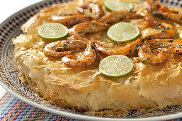 Close-up photo of Moroccan Seafood Bastilla, a savory seafood pie wrapped in crispy paper-thin pastry. The pie is garnished with cooked shrimp and thin slices of lemon.