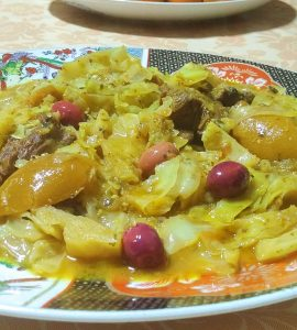 Moroccan stewed cabbage is served on a decorated plate. Pieces of meat can be seen in the cabbage, and the dish is decorated with wedges of preserved lemon and olives.