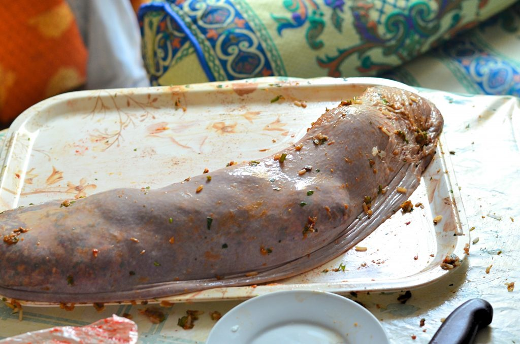 A stuffed spleen sits on a plastic tray. It looks like a very large uncooked sausage.