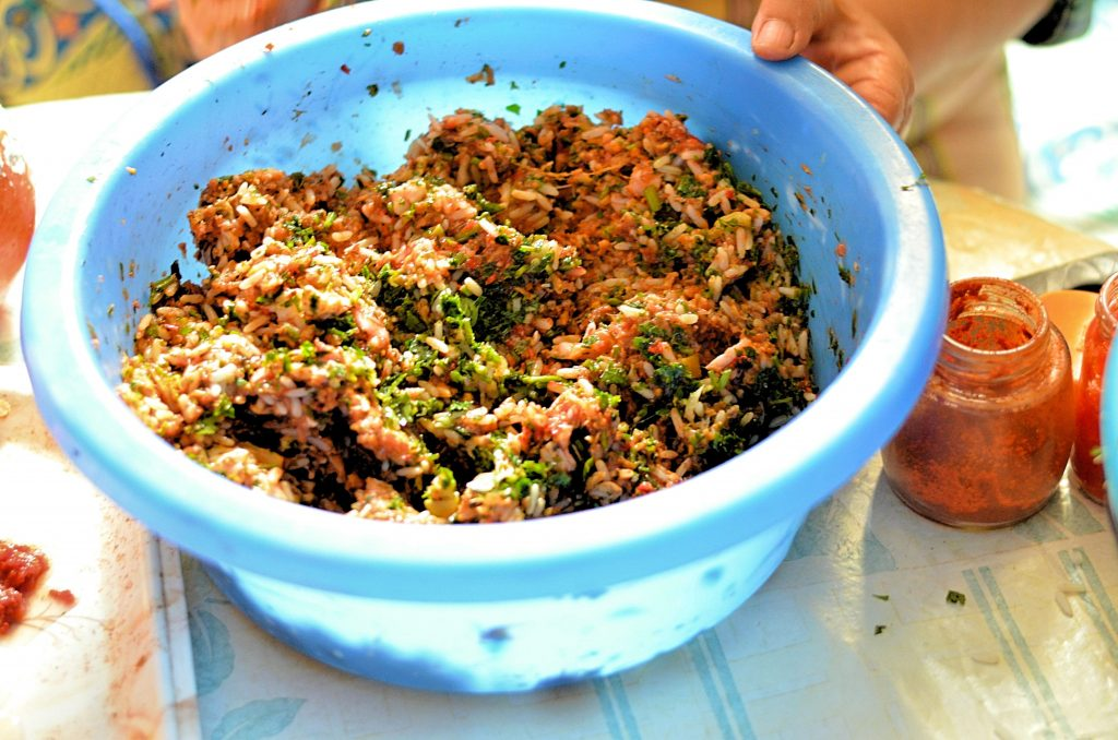 A mixture of seasoned raw ground beef and rice sits in a blue plastic bowl.