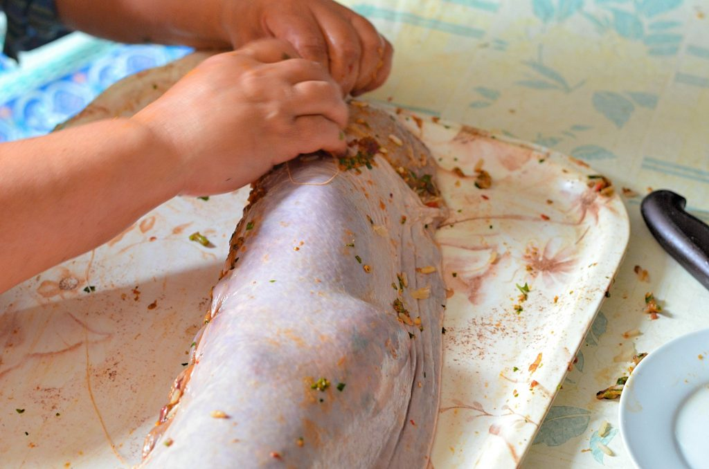A woman's hands are seen sewing a stuffed spleen shut.