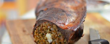 Close-up view of veal spleen stuffed with a Moroccan mixture of kefta and rice sits on a wooden cutting board. The spleen has been sliced to reveal the filling. A knife sits on the cutting board next to the stuffed spleen.