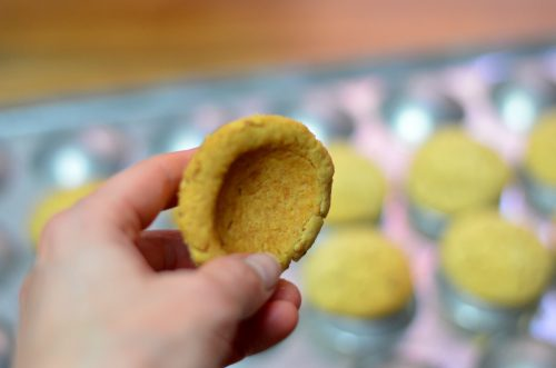 A hand holds amolded shortbread cookie to reveal its concave underside.