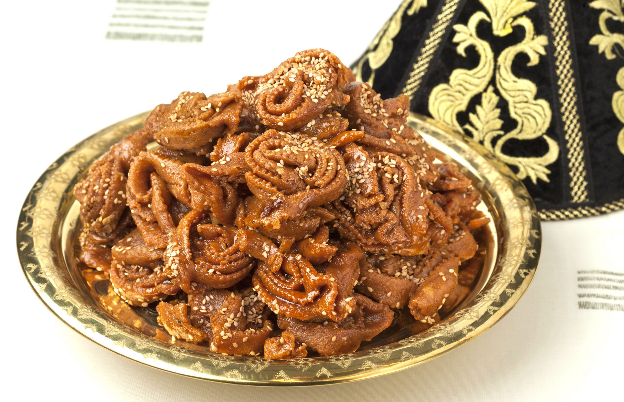 A mound of Moroccan chebakia cookies are mounded on a decorative metal tray.