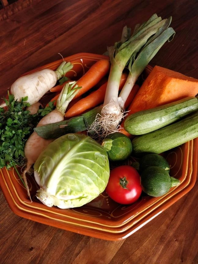 an assortment of fresh mixed vegetables in a large ceramic dish