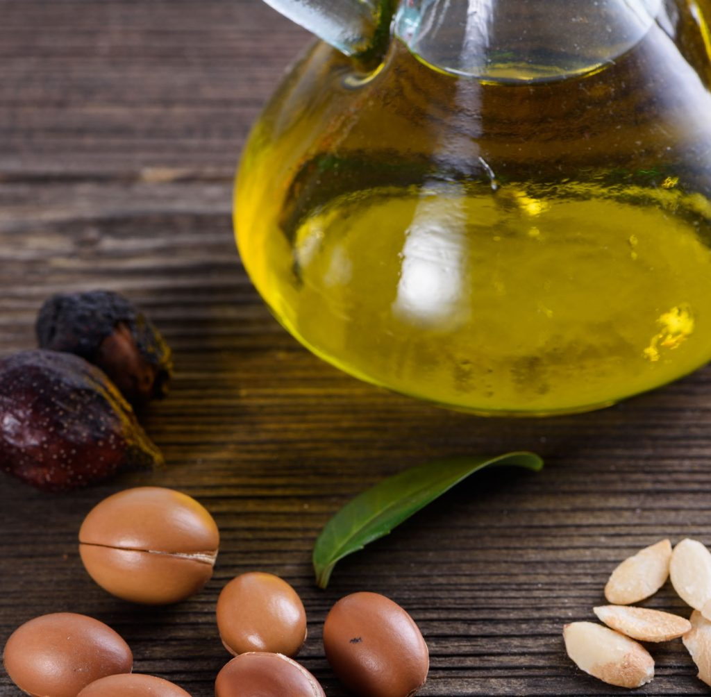 Argan fruit, nuts and kernels sit alongside cosmetic argan oil.