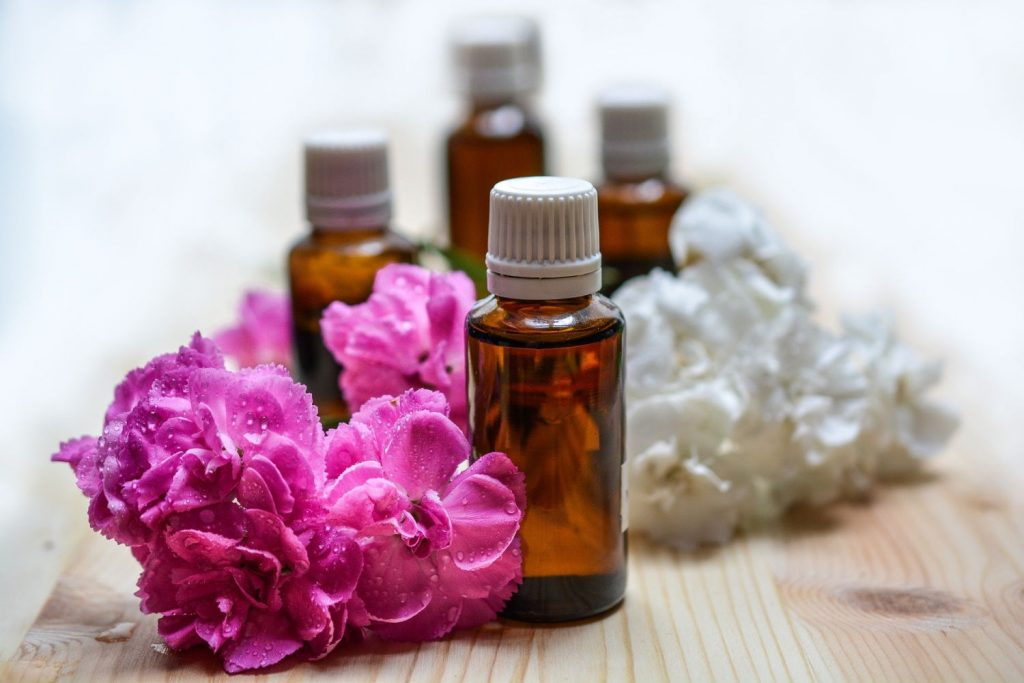 Small bottles of essential oils sit among flower blossoms.