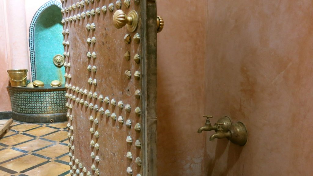 Interior view of a hammam showing wall faucets, studded door and tiled room.