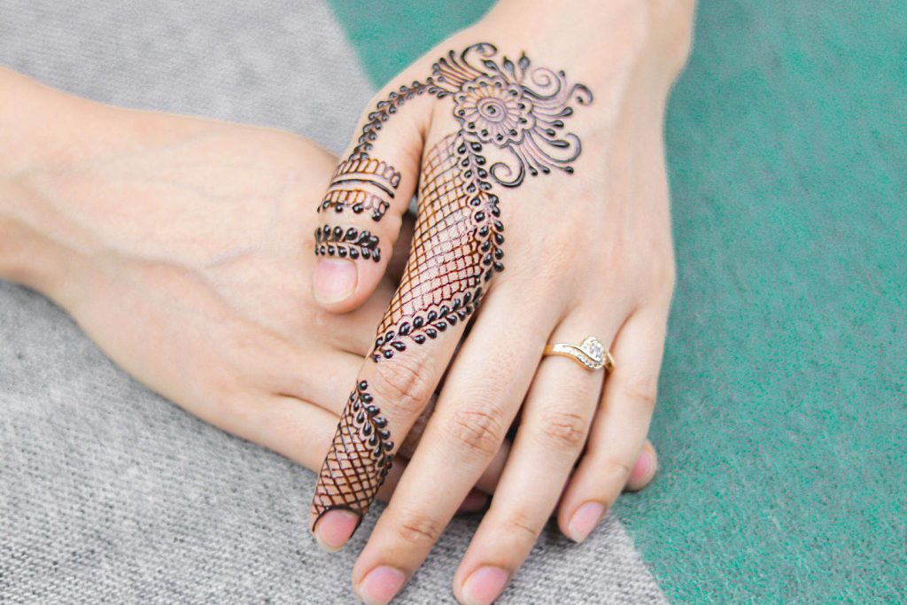 A woman's hands are shown. One has a henna tattoo.