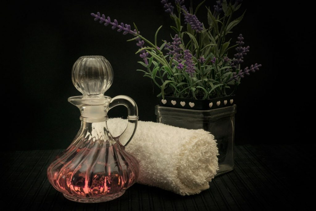 Bottle of scented water, rolled hand towel, and boxed lavender plant.