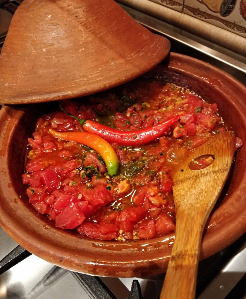 Homemade tomato sauce cooking in a tagine.